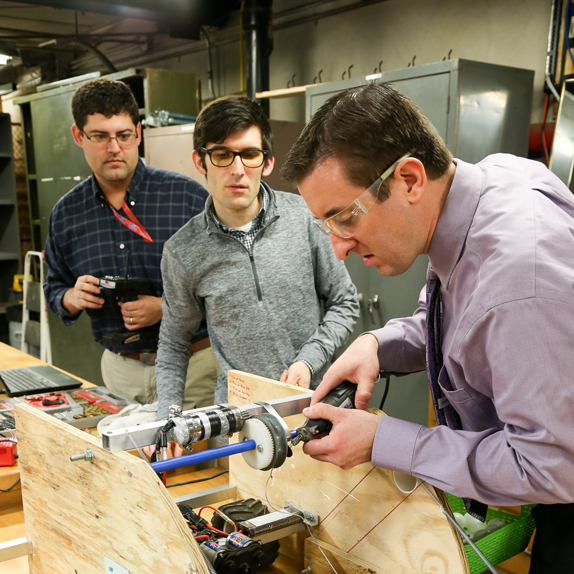 Engineering Students work with Professor in lab