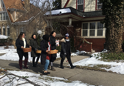 Before the pandemic, groups of students got to know University neighbors as they made food deliveries, as seen here. They are now leaving packages on the porches.