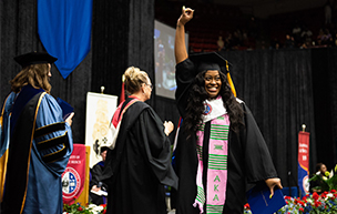 A student celebrates on stage during the Detroit Mercy commencement ceremony.