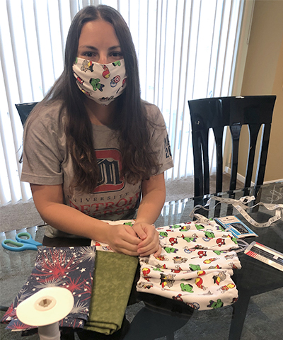 Physician Assistant student Jessica Sherbin poses in front of the masks she's made to donate.