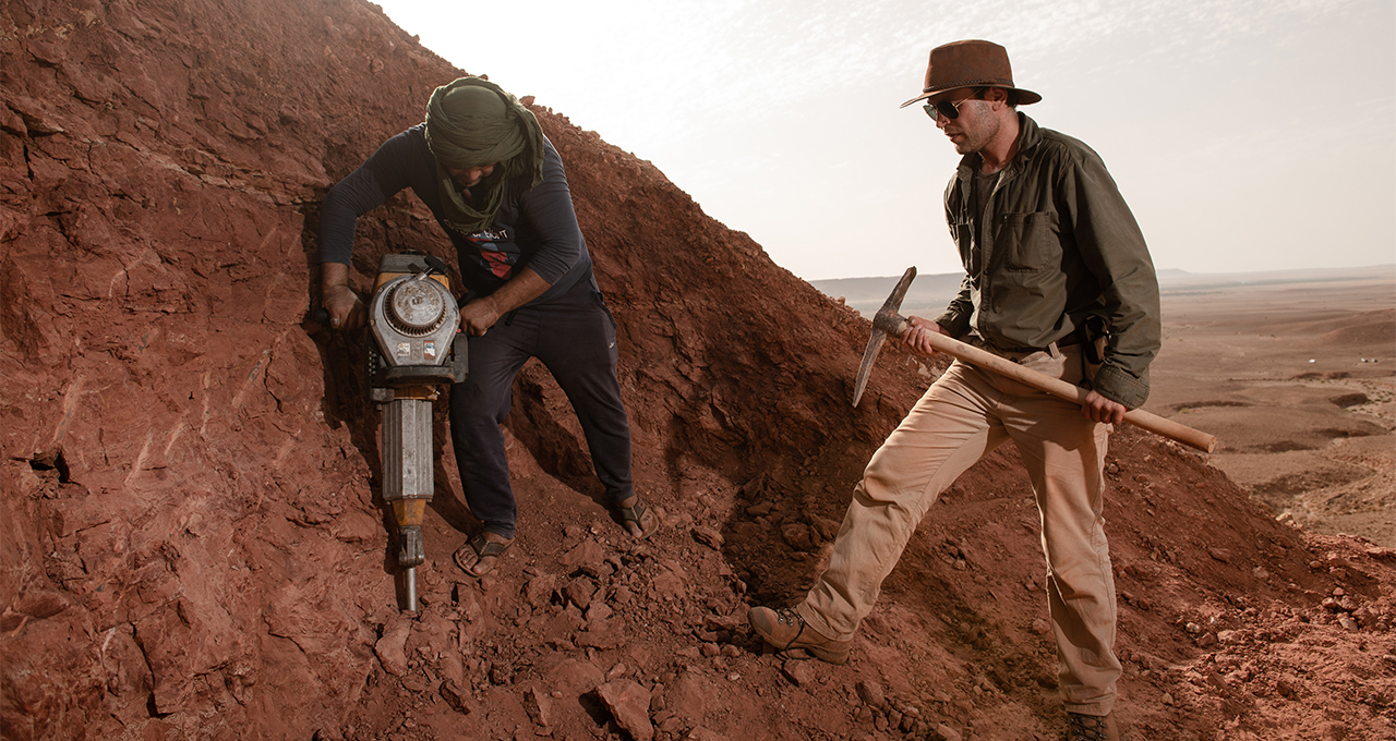 University of Detroit Mercy professor Nizar Ibrahim holds pickaxe at dig site with fellow explorer.