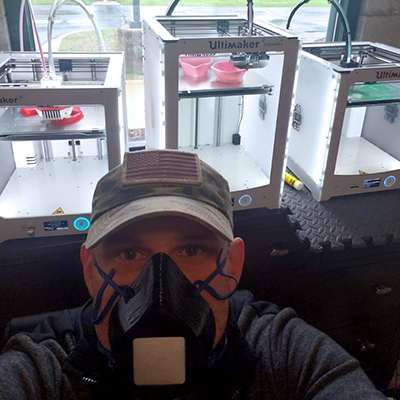 Nick Summerlee wears a mask he made and poses behind his 3-D printers.