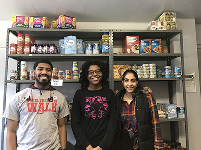 Three students pose in front of The HIVE's food bank. The HIVE is looking for ways to provide much needed services for students when no one is on campus.