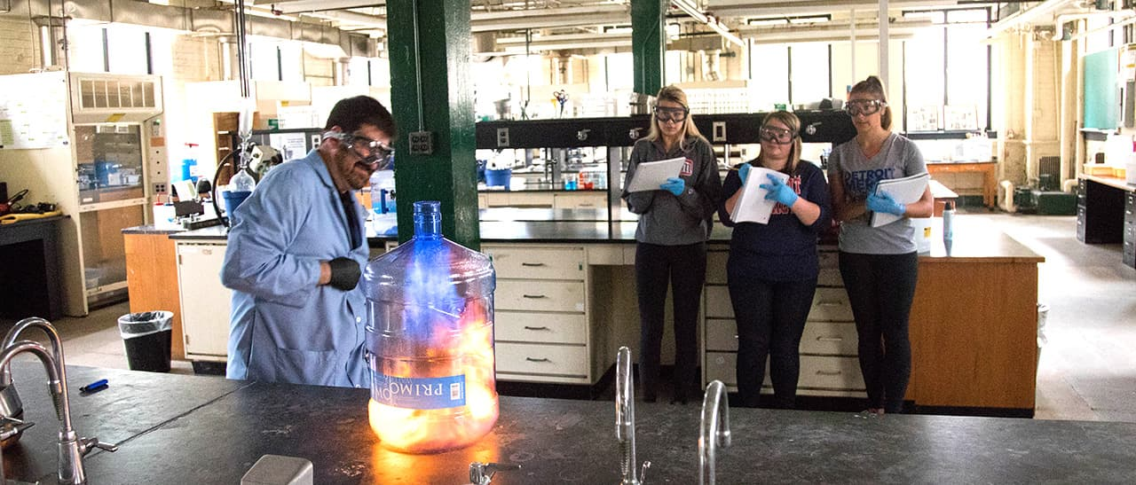chem student with professor making a fireball in a clear container